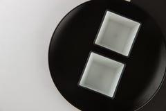 Um número placas lisas e de copos no fundo preto e branco Imagens de Stock