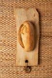 Um naco de pão no fundo da grama do weave que mostra a textura fotografia de stock royalty free