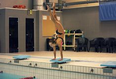 Um nadador fêmea, esse pronto para saltar na piscina do esporte interno estar nos braços com pés acima imagem de stock