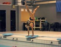 Um nadador fêmea, esse pronto para saltar na piscina do esporte interno estar nos braços com pés acima fotografia de stock