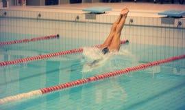 Um nadador fêmea, esse salto e mergulho na piscina do esporte interno Mulher desportiva fotos de stock