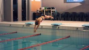 Um nadador fêmea, esse salto e mergulho na piscina do esporte interno Mulher desportiva foto de stock