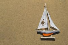Um navio alaranjado do brinquedo com uma vela branca est? encontrando-se na areia textured ? direita foto de stock