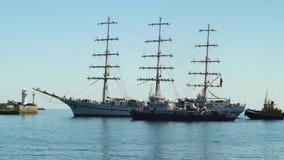 Um navio bonito da três-navigação está navegando ao porto e é acompanhado de dois barcos de reboco em Yalta 4k vídeos de arquivo
