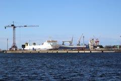 Um navio de carga entrou no porto de Dunkirk ocupou para ser carregado por guindastes Fotos de Stock Royalty Free