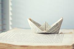 Um navio de papel é enviado ao trajeto do conhecimento e as palavras no mar registram o fundo fotos de stock royalty free