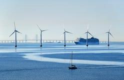 Um navio de passageiro muito grande e um veleiro pequeno passam turbinas eólicas a pouca distância do mar perto da ponte de Oresu foto de stock royalty free