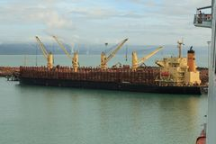 Um navio do portador de maioria que toma em uma grande carga dos logs imagem de stock