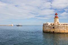 Um navio entre a luz do quebra-mar de Ricasoli e o St Elmo Breakwater Head Light, Valletta, Malta imagem de stock royalty free