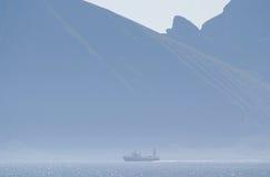 Um navio na frente das montagens envolvidas na névoa. Fotos de Stock
