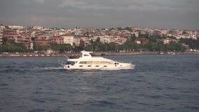 Um navio pequeno que flutua lentamente na área costal perto da cidade Nas casas puras bonitas do horizonte filme