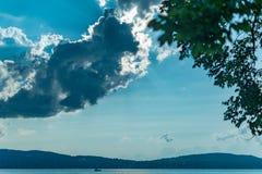 Um navio pequeno viaja ao longo de Hudson River, abaixo de um céu azul bonito e das nuvens retroiluminados pelo sol, Sleepy Hollo imagem de stock royalty free