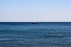 Um navio solitário no horizonte de mar imagens de stock royalty free