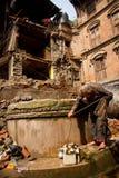 Um Nepali que idoso a senhora usa bem entre o terremoto arruina i Imagens de Stock