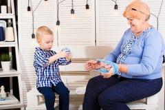 Um neto pequeno ajuda a avó a enrolar a linha em um emaranhado fotos de stock