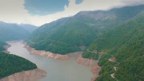 Um ônibus que viaja em uma estrada da montanha ao longo do rio, montanha, fotografia aérea video estoque