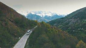 Um ônibus que viaja em uma estrada da montanha, tiro do ar vídeos de arquivo
