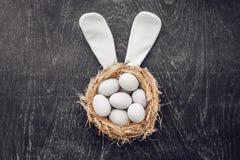 Um ninho com os três ovos da páscoa e orelhas brancos do coelho em casa no dia da Páscoa Comemorando a Páscoa na mola Ovos da pin Imagens de Stock Royalty Free