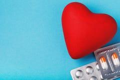 Um objeto na forma de um coração e de comprimidos em uma tabela azul fotos de stock