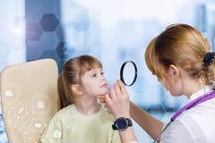 Um oftalmologista que olha os olhos pequenos da criança através da lente de aumento fotos de stock