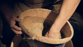 Um oleiro do homem começa misturar a argila em uma cubeta vídeos de arquivo