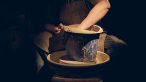 Um oleiro senta-se na obscuridade e mistura-se a argila vídeos de arquivo