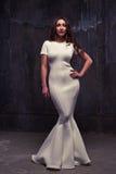 Um olhar profundo fascinante da jovem mulher na moda em d de nivelamento branco Imagem de Stock Royalty Free