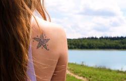 Um ombro da jovem mulher com tatuagem Fotos de Stock