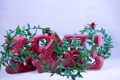 Um ornamento cerâmico vermelho das cartas de amor com os ouropéis indicados em um fundo branco fotografia de stock
