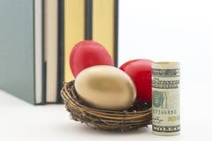 Um ouro e dois ovos de ninho vermelhos com dólar ereto Imagens de Stock Royalty Free