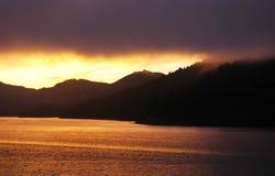 Um ouro e um por do sol enevoado sobre montanhas e um lago Fotos de Stock