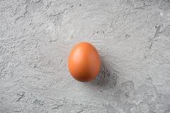 Um ovo bege no alimento de pedra cinzento do conceito do fundo é solidão, a comparação é frágil e durável imagem de stock royalty free