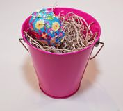 Um ovo da páscoa em uma cubeta cor-de-rosa Fotos de Stock Royalty Free