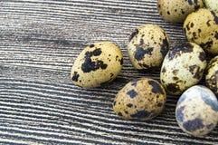 Um ovo de codorniz em um fundo branco, um ovo do ` s das codorniz, muitos ovos de codorniz em um assoalho de madeira Fotografia de Stock