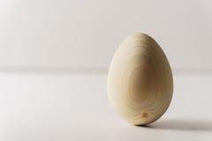Um ovo de madeira no fundo branco fotos de stock