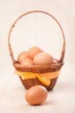 Um ovo na frente de pouca cesta com curva amarela no tabl de madeira Imagem de Stock