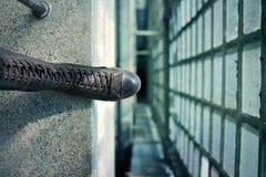 Um pé da sapata na borda de um assoalho da construção concreta foto de stock royalty free
