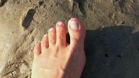 Um pé desencapado fêmea está na areia molhada e aumenta os dedos do pé filme