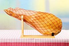 Um pé dianteiro de um presunto espanhol de Serrano na toalha de mesa listrada vermelha a fotos de stock royalty free