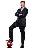 Um pé ereto do homem de negócio na bola de futebol Imagens de Stock Royalty Free