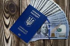 Um pacote de cédulas de 100 dólares em um passaporte estrangeiro azul biométrico de um cidadão de Ucrânia fotografia de stock