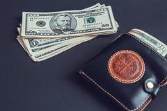 Um pacote de cédulas do dólar e de uma carteira de couro marrom foto de stock