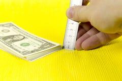 Um pacote de dólares e de uma régua Imagens de Stock Royalty Free
