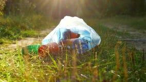 Um pacote do lixo plástico encontra-se na floresta em uma estrada de floresta, na poluição da natureza, no lixo e na natureza, o  vídeos de arquivo