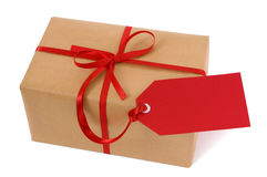 Um pacote ou presente do papel marrom amarrado com a etiqueta vermelha da fita e do presente isolada no fundo branco Imagens de Stock Royalty Free