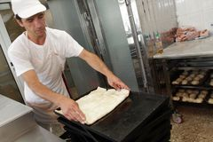 """Um padeiro amassa a massa para a torta do queijo com rolo e farinha na padaria na cidade †de Sófia, Bulgária """"4 de setembro de  Imagem de Stock Royalty Free"""