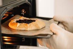 Um padeiro fêmea põe o galette com os corintos pretos no forno Receita da torta Cozimento caseiro fotografia de stock royalty free