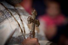 Um padre guarda uma cruz imagens de stock