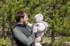 Um pai com um beb? em seus bra?os est? andando no parque Um homem novo com uma barba guarda uma menina da crian?a 9 meses fotografia de stock