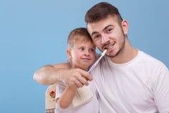 Um pai com um filho pequeno, tendo o divertimento junto, pai está ensinando seu filho escovar os dentes com uma escova de dentes fotografia de stock